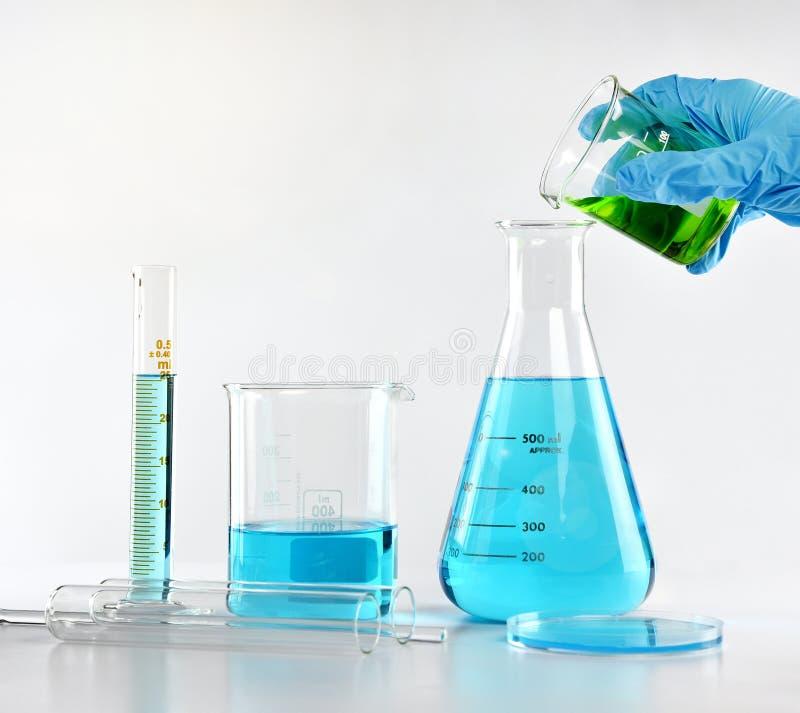 Forskaren med utrustning och vetenskap experimenterar, laboratoriumglasföremål som innehåller giftlig kemisk flytande royaltyfri bild