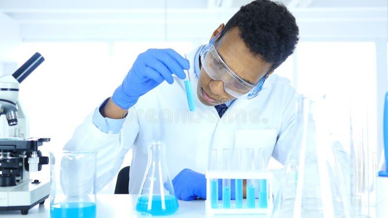 Forskningforskare Looking på reaktion i provrör i laboratorium arkivfoton