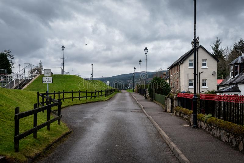 FORT AUGUSTUS, SCOTLAND, DECEMBER 17, 2018: View of the road aside the Caledonian Canal while a bird flies on a cloudy day. A stock photos