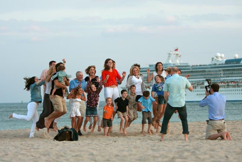 Den stora familjen som hopp luftar in stundfotografen, tar fotoet royaltyfria foton