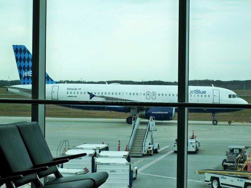 Fort Myers, FLA, EUA, maio 7,2019 Plano de Jet Blue que entra o terminal vista da janela ao esperar para embarcar o plano fotos de stock