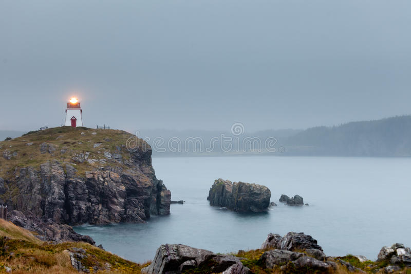 Fort Point Lighthouse Trinity Newfoundland Canada. Trinity Harbour Lighthouse on Fort Admirals Point in foggy twilight, Bonavista Peninsula, Newfoundland, NL royalty free stock photography