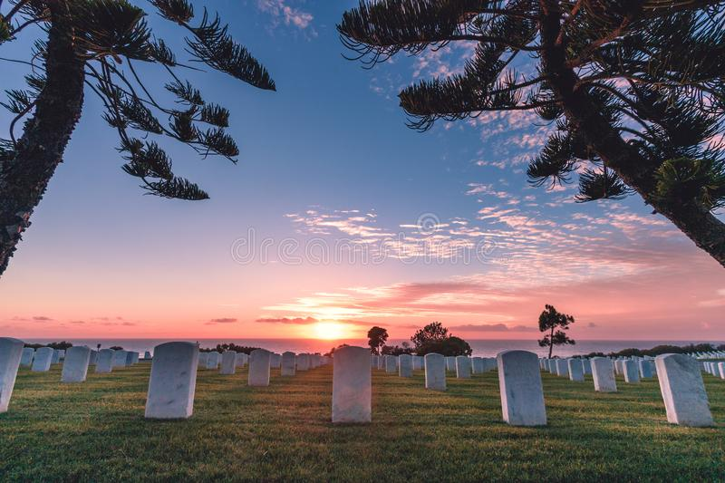 Fort Rosecrans National Cemetery, Point Loma, San Diego, California, USA. Monument headstones along the coast during a pink, orange, and blue sunset with stock photo