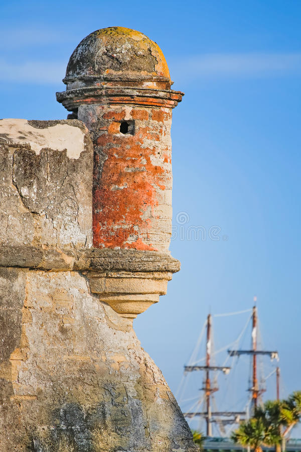 Fort with Sailing Ship. A round corner sentry box, on an old St. Augustine, Florida Spanish fort called the Castillo de San Marcos, is backed by the tall masts royalty free stock images
