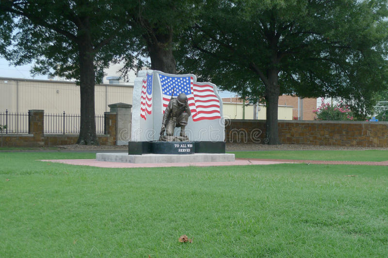 Fort Smith National Cemetery memorial statue with flag. National Cemetery in Fort Smith, Arkansas includes a monumental statue of a soldier kneeling with a flag royalty free stock photo
