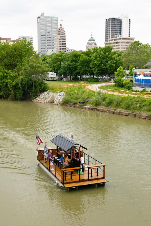 Fort Wayne. Indiana, USA - June 8, 2019: Barge Bar, carrying people drinking, traveling on St Marys River, with city skyline at the background stock image