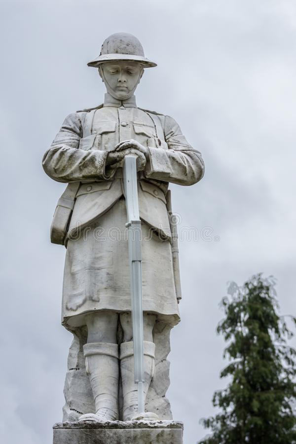War memorial in Fort William, Scotland. Fort William, Scotland - June 11, 2012: Closeup of white stone war memorial statue on The Parade against gray sky. Shows stock photo