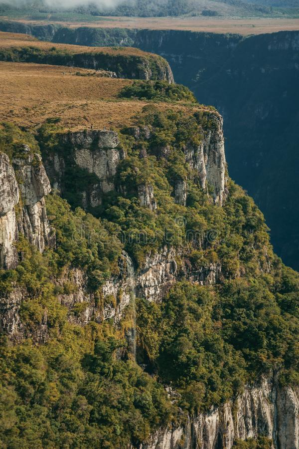 Fortaleza Canyon with steep cliffs and waterfall. Fortaleza Canyon with steep rocky cliffs covered by forest and waterfall coming from the edge near Cambara do stock photo