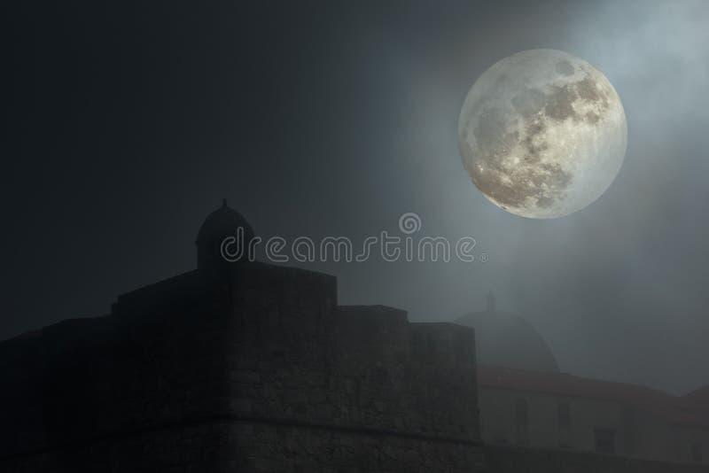 Fortaleza velha em uma noite nevoenta foto de stock