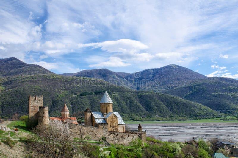 Fortaleza velha na costa contra o contexto das montanhas, um céu bonito da mola, Ananuri imagens de stock royalty free