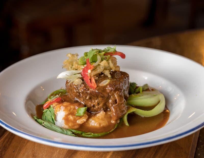 Fortalezca el curry de Rendang en el cuenco blanco en la tabla del pub foto de archivo