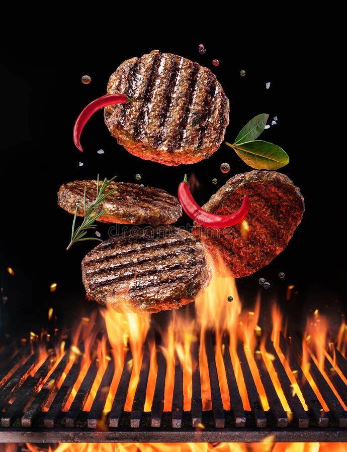 Fortalezca la carne molida en la hamburguesa con las especias vuelan sobre el fuego llameante de la barbacoa de la parrilla fotografía de archivo