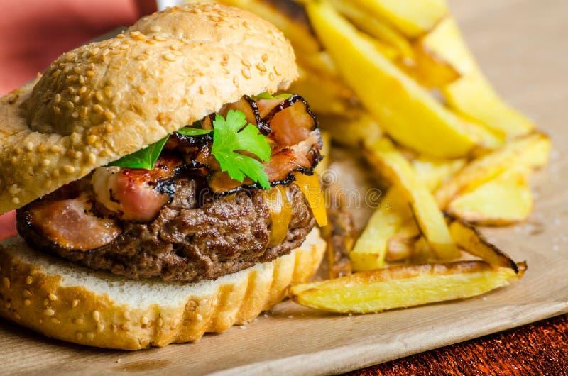 Fortalezca la hamburguesa con el tocino, Cheddar, fritadas hechas en casa fotografía de archivo