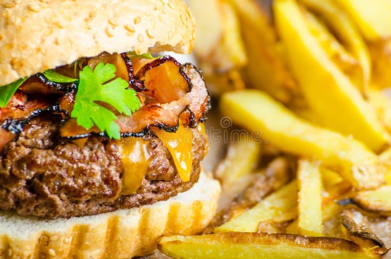 Fortalezca la hamburguesa con el tocino, Cheddar, fritadas hechas en casa fotos de archivo libres de regalías