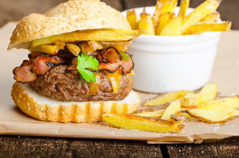 Fortalezca la hamburguesa con el tocino, Cheddar, fritadas hechas en casa fotos de archivo