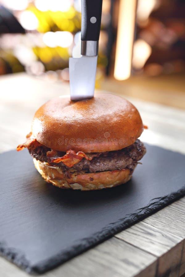 Fortalezca la hamburguesa con tocino Chuleta asada a la parrilla de la carne de vaca en un bollo foto de archivo