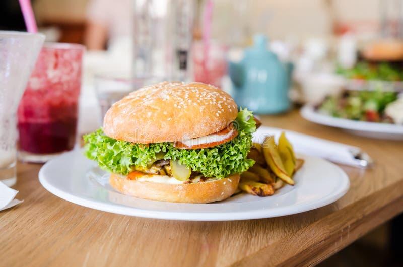 Fortalezca la hamburguesa con tocino, queso y ensalada imagen de archivo