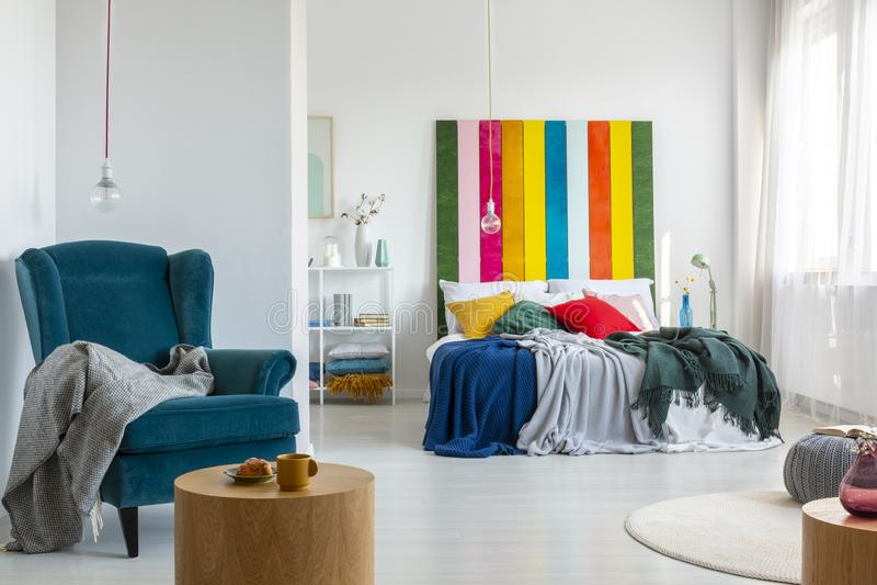 Forte accento di colore in camera da letto luminosa interna con il tavolino da salotto, il letto a due piazze, la poltrona e lo s fotografie stock