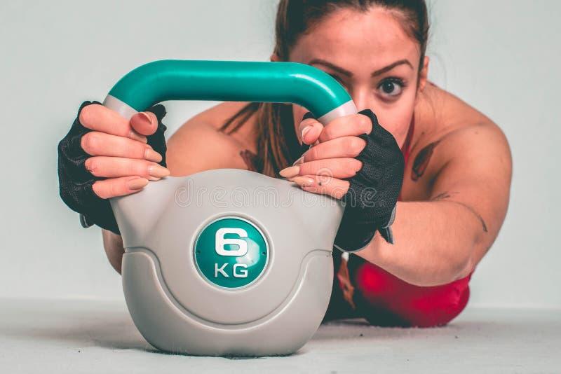 Forte addestramento della donna con il kettlebell - Immagine immagini stock libere da diritti