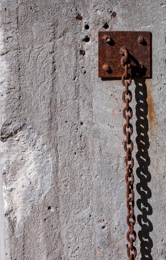 Forte catena arrugginita che appende lungo la parete fotografia stock libera da diritti