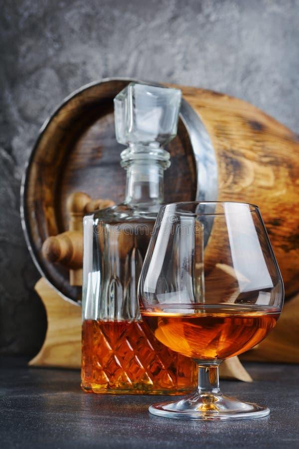 Forte cognac della bevanda alcolica in vetro della ventosa con il decantatore a cristallo e barilotto di legno d'annata in cantin fotografia stock
