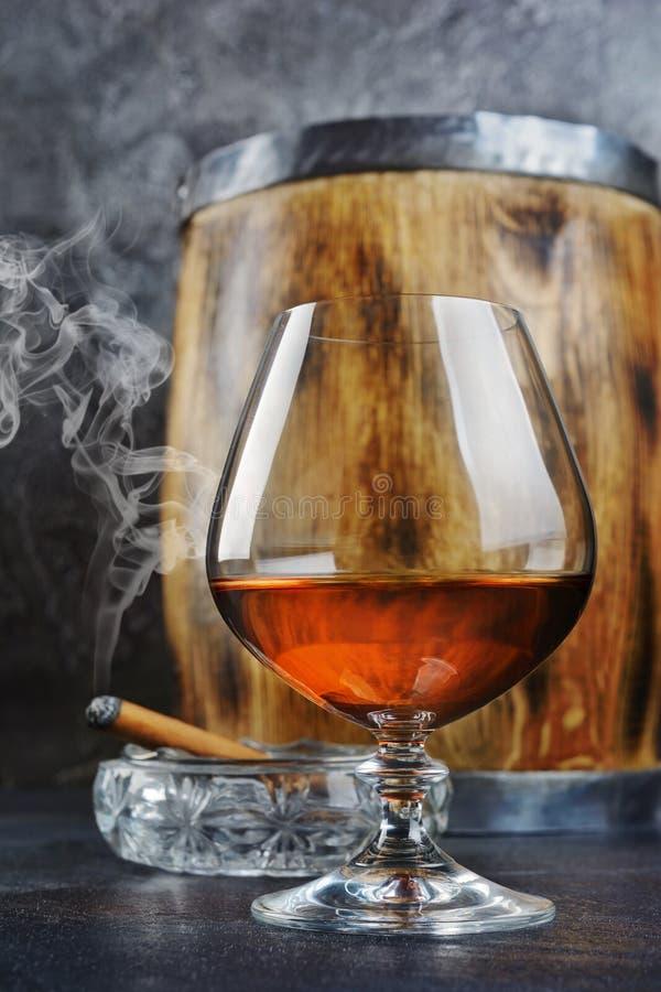 Forte cognac della bevanda alcolica in vetro della ventosa con il sigaro di fumo in portacenere a cristallo ed in barilotto di le immagine stock libera da diritti