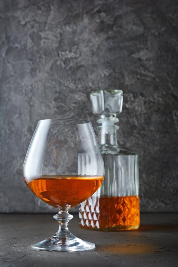 Forte cognac della bevanda alcolica in vetro della ventosa e decantatore dell'a cristallo fotografia stock libera da diritti