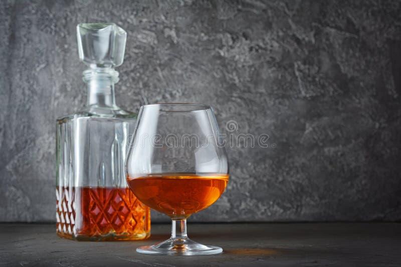 Forte cognac della bevanda alcolica in vetro della ventosa e decantatore dell'a cristallo fotografia stock