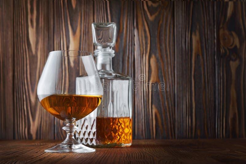 Forte cognac della bevanda alcolica in vetro della ventosa e decantatore dell'a cristallo immagine stock libera da diritti