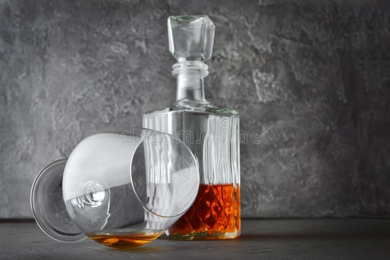 Forte cognac della bevanda alcolica in vetro della ventosa e decantatore di menzogne dell'a cristallo immagine stock