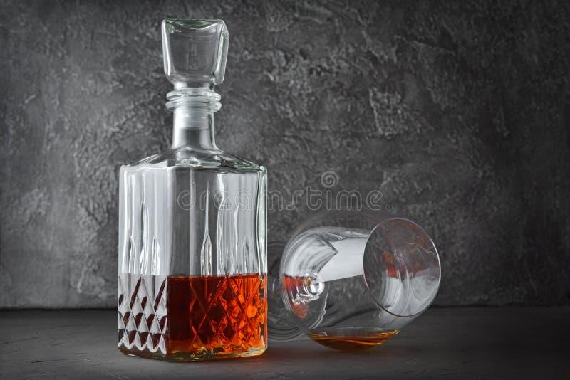 Forte cognac della bevanda alcolica in vetro della ventosa e decantatore di menzogne dell'a cristallo fotografia stock