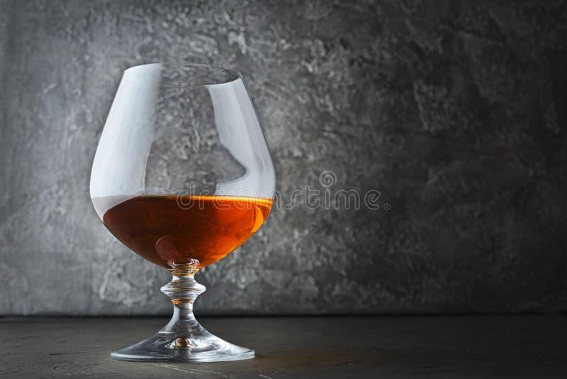 Forte cognac della bevanda alcolica in vetro della ventosa per avere un sapore fotografia stock libera da diritti