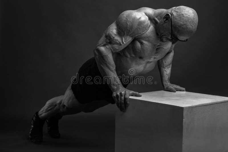 Forte culturista atletico brutale dell'uomo che posa nello studio fotografia stock