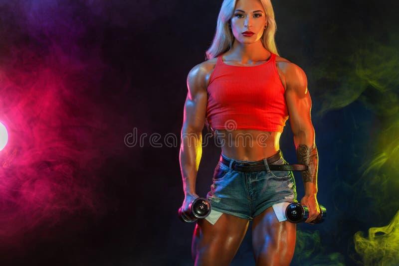 Forte culturista atletico della donna con le teste di legno su fondo scuro che dura in abiti sportivi Motivazione di sport e di f fotografie stock libere da diritti