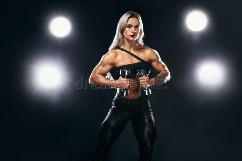 Forte culturista atletico della donna sugli steroidi con le teste di legno su fondo scuro che dura in abiti sportivi Forma fisica fotografia stock libera da diritti