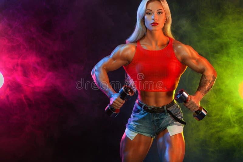 Forte culturista atletico della donna sugli steroidi con le teste di legno su fondo scuro che dura in abiti sportivi Forma fisica fotografie stock libere da diritti