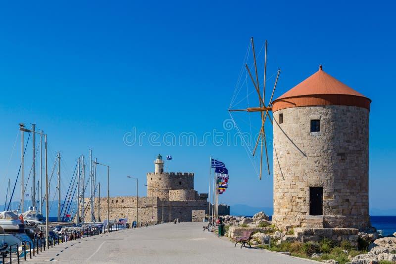 Forte de Nikolas de Saint e moinho de vento medieval no porto de Mandraki, o Rodes foto de stock