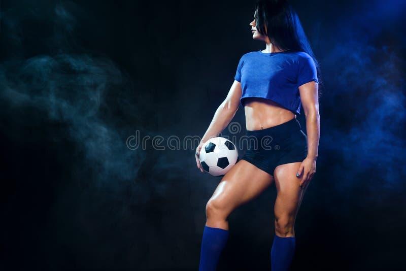 Forte donna atletica con pallone da calcio su fondo nero Concetto di sport Tifoso fotografia stock libera da diritti
