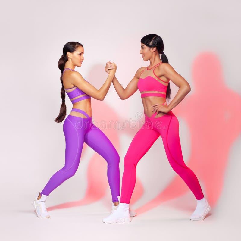 Forte donna atletica, facente esercizio sugli abiti sportivi d'uso del fondo bianco Motivazione di sport e di forma fisica fotografie stock libere da diritti