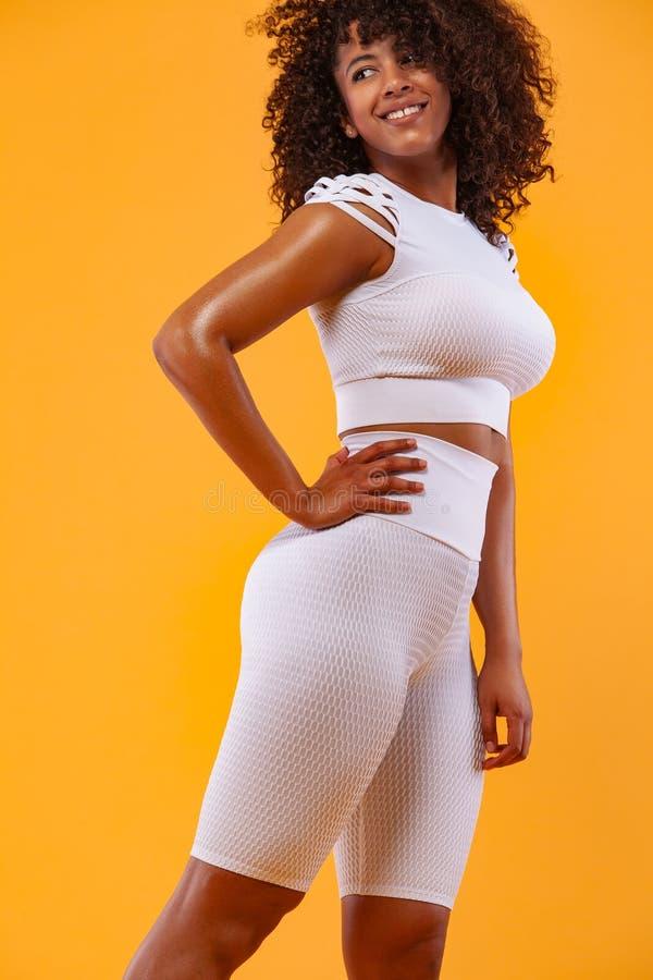 Forte donna atletica sorridente con pelle nera e capelli ricci, facenti esercizio sugli abiti sportivi d'uso del fondo bianco fotografia stock