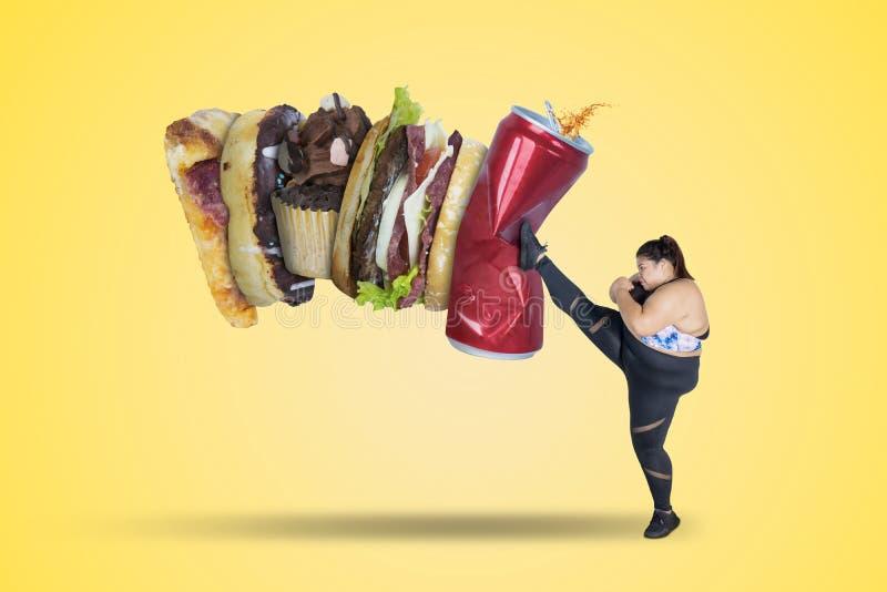 Forte donna che dà dei calci ai pasti non sani immagine stock