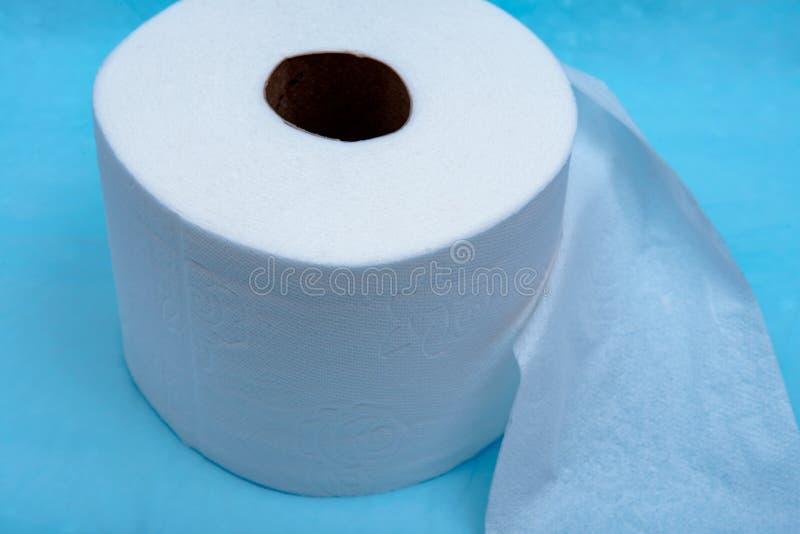 Forte e carta igienica bianca assorbente molle isolata sul blu immagini stock libere da diritti