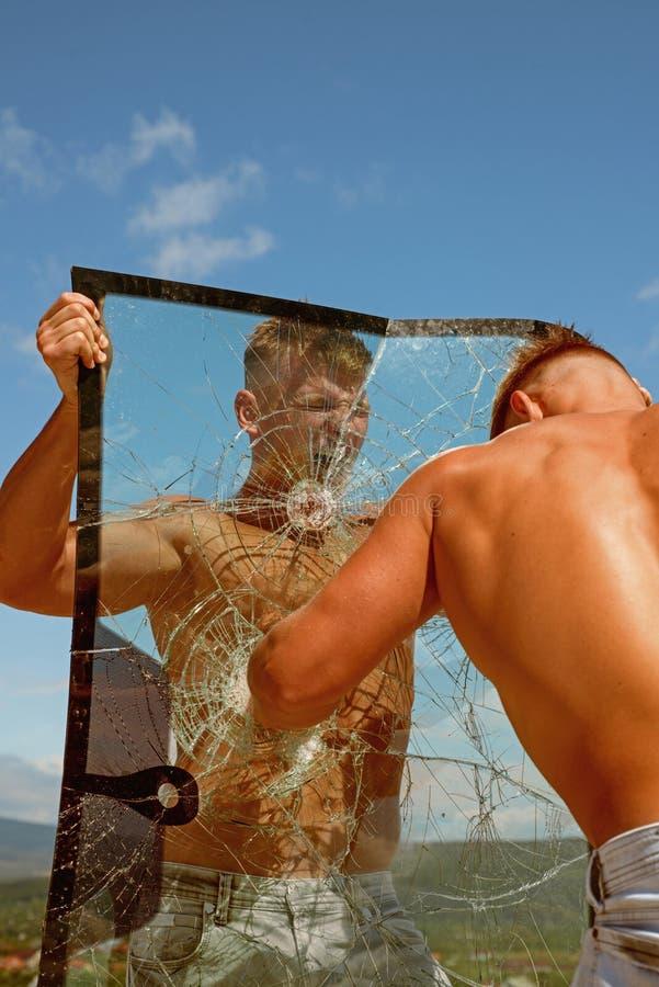 Forte e completo da energia Os homens dos gêmeos perfuram um vidro Os concorrentes dos gêmeos mostram a força e o poder musculare foto de stock