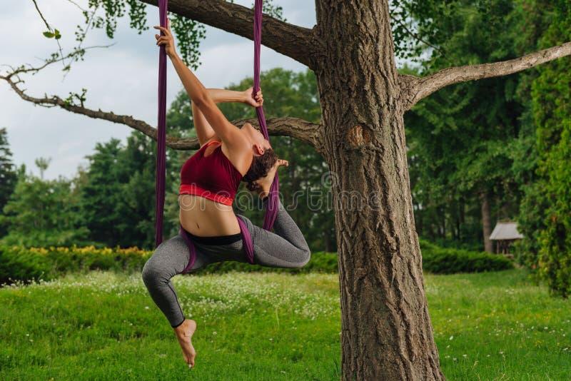 Forte e donna in buona salute di yoga che dà la classe del padrone di yoga della mosca fotografie stock