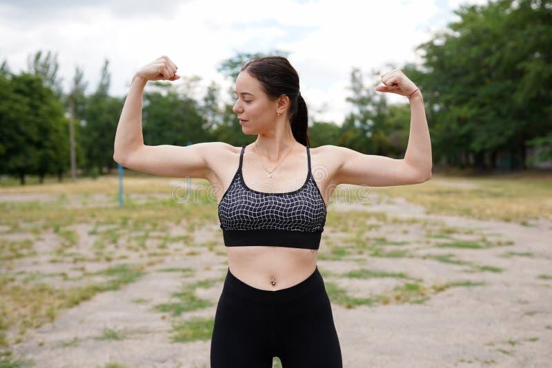 Forte ed energia Donna castana abbastanza giovane che mostra bicipite sul suo braccio immagine stock libera da diritti
