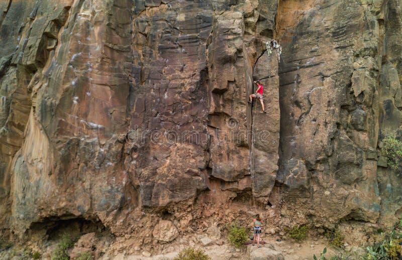 Forte homem escalando uma parede de rocha num canyon - Formação climática ao ar livre num ponto rochoso - Viagens, adrenalina e e foto de stock royalty free