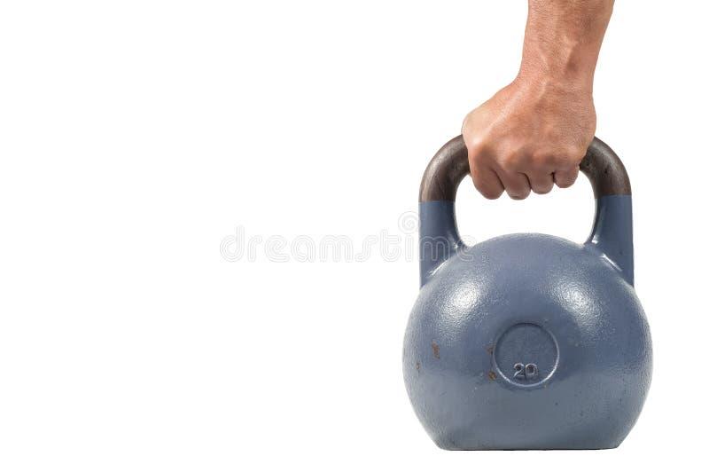 Forte mano muscolare dell'uomo con i muscoli che giudicano kettlebell pesante blu parzialmente isolato su fondo bianco immagine stock libera da diritti