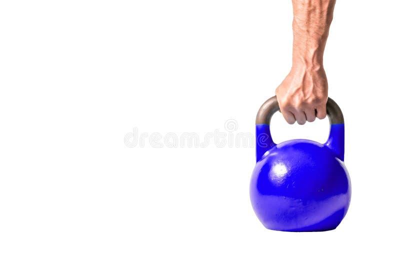 Forte mano muscolare dell'uomo con i muscoli che giudicano kettlebell pesante blu scuro parzialmente isolato su fondo bianco fotografie stock libere da diritti