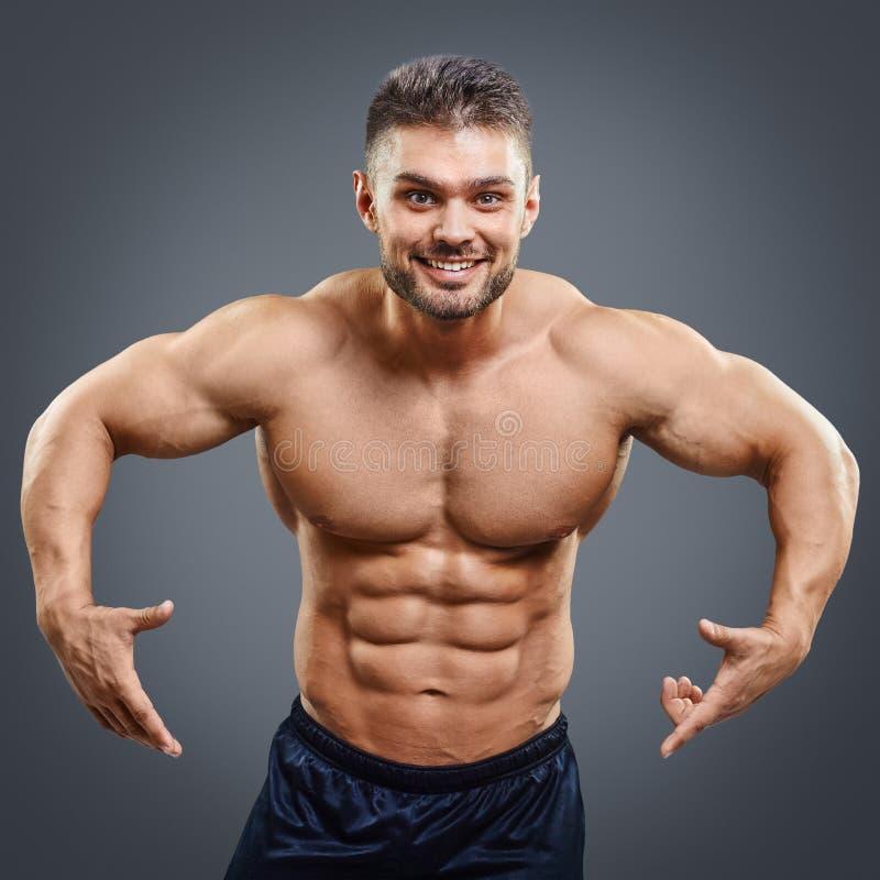 Forte modello atletico Torso di forma fisica dell'uomo che indica giù fotografia stock