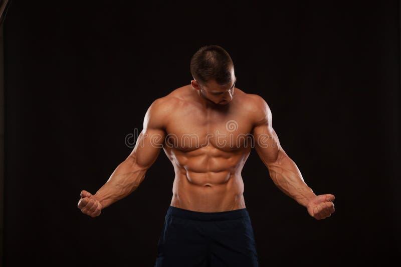 Forte modello atletico Torso di forma fisica dell'uomo che mostra l'ABS di addominali scolpiti isolato su fondo nero con copyspac fotografia stock libera da diritti